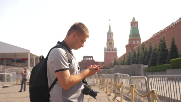 Travel and technology. Happy tourist man looks the navigator smartphone taking selfie with backpack. slow motion video. on Red Square in Moscow, Russia Kremlin. tourist journey travel man in Russia