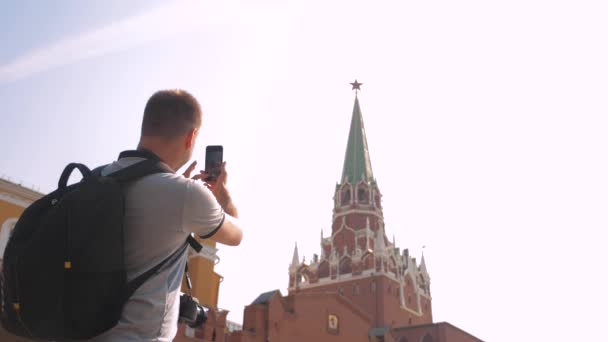Travel and technology. lifestyle Happy tourist man looks the navigator smartphone taking selfie with backpack. slow motion video. on Red Square in Moscow, Russia. tourist journey travel man in Russia