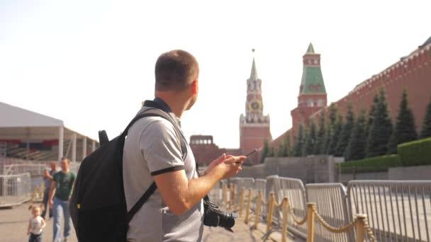 Utazási és a technológia. Ember boldog turisztikai néz ki a navigátor smartphone, figyelembe véve a selfie, a hátizsák. Slow motion videót. a Vörös téren Moszkva, Oroszország-Kreml. turisztikai utazás utazási férfi életmód