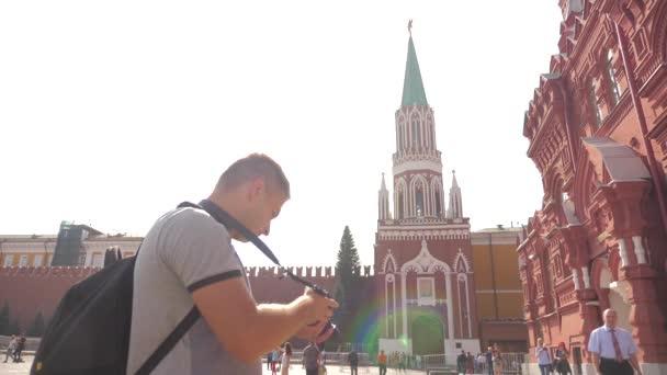 Utazási és a technológia. Boldog turisztikai ember néz ki a navigátor smartphone Állami Történeti Múzeum figyelembe selfie a hátizsák. Slow motion videót. a Vörös téren Moszkva, Oroszország-Kreml. turisztikai utazás