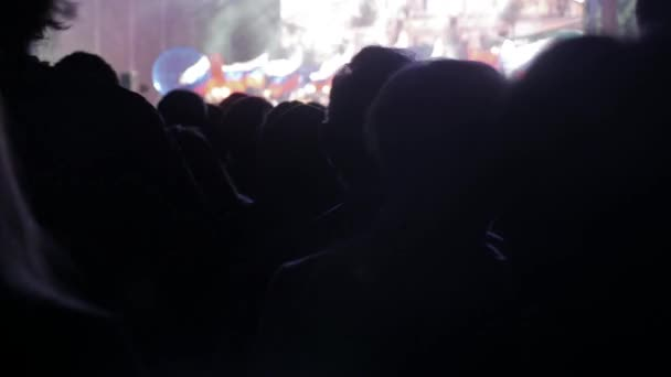 Crowd at concert. Cheering crowd in front of bright colorful stage lights. silhouettes of concert crowd in front of bright stage lights. crowd of people at a concert concept lifestyle night