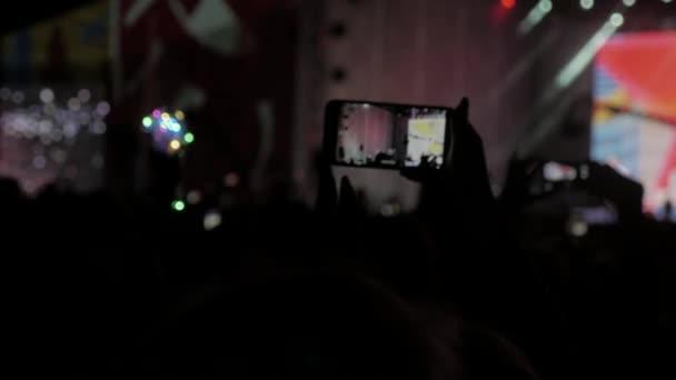 Menge Leute beim Musikkonzert. Jubelnde Menge nimmt Bilder auf einem Smartphone vor leuchtend bunte Bühnenbeleuchtung. Silhouetten von Konzert-Publikum in Lebensstil vordere Beleuchtung hell. Menge