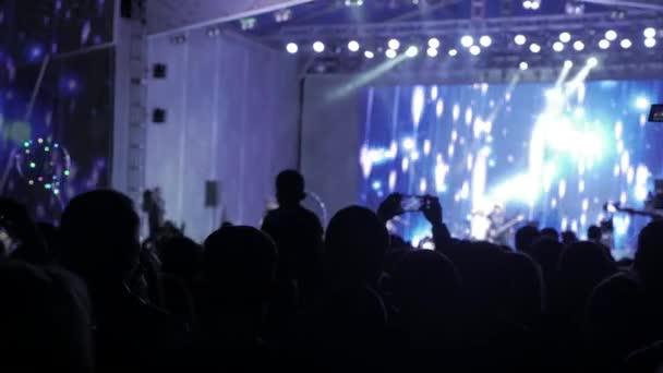 Menge Leute beim Musikkonzert. Jubelnde Menge nimmt Bilder auf einem Smartphone vor leuchtend bunte Bühnenbeleuchtung. Silhouetten von Konzert drängen sich vor hellen Lebensstil Bühnenbeleuchtung. Menge