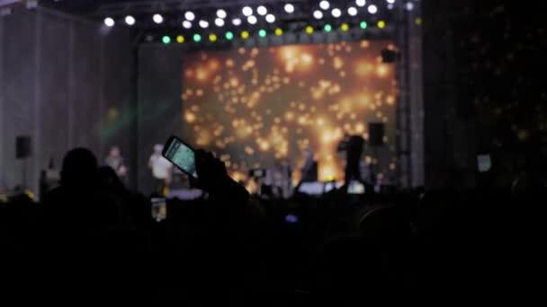 Menge Leute beim Musikkonzert. Jubelnde Menge fotografiert Lifestyle auf einem Smartphone vor leuchtend bunte Bühnenbeleuchtung. Silhouetten von Konzert drängen sich vor hellen Bühnenbeleuchtung. Menge