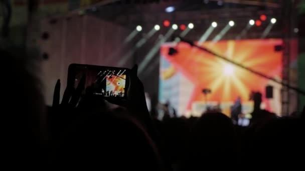 Menge Leute beim Musikkonzert. Jubelnde Menge nimmt Bilder auf einem Smartphone vor leuchtend bunte Bühnenbeleuchtung. Silhouetten von Konzert drängen vor Lebensstil Bühnenbeleuchtung von hell. Menge