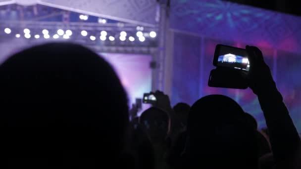 Tömeg: zene koncertet. Éljenző tömeg életmód előtt fényes színes rivaldafény. sziluettek koncert tömeg előtt fényes színpadon lights. tömeg ember, egy koncert koncepció éjjel