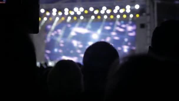 Menge Leute beim Musikkonzert. Jubelnde Menge nimmt Bilder auf einem Smartphone vor leuchtend bunte Bühnenbeleuchtung. Silhouetten von Konzert drängen sich vor Lebensstil helle Beleuchtung. Menge