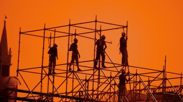 silueta dělníci při západu slunce stavitelé shromažďovat design. stavební dělníci životní styl koncepce budování silueta muže zpomalené video skupiny
