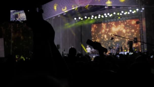 Menge Leute beim Musikkonzert. Lebensstil Jubel Masse nimmt Bilder auf einem Smartphone vor leuchtend bunte Bühnenbeleuchtung. Silhouetten von Konzert drängen sich vor hellen Bühnenbeleuchtung. Menge