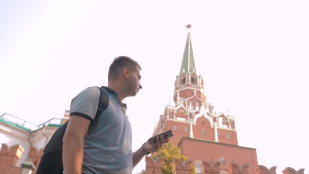 Travel and technology. Happy tourist man looks the navigator smartphone taking selfie with backpack. slow motion video. on Red Square in Moscow lifestyle, Russia. tourist journey travel man in Russia