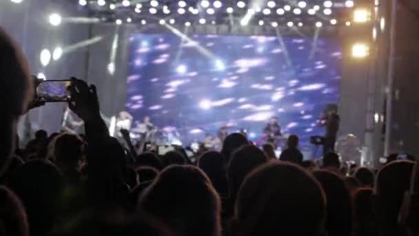 Menge Leute beim Musikkonzert. Jubelnde Menge nimmt Bilder auf einem Smartphone vor leuchtend bunte Bühnenbeleuchtung. Silhouetten von Lebensstil Konzert drängen sich vor hellen Bühnenbeleuchtung. Menge