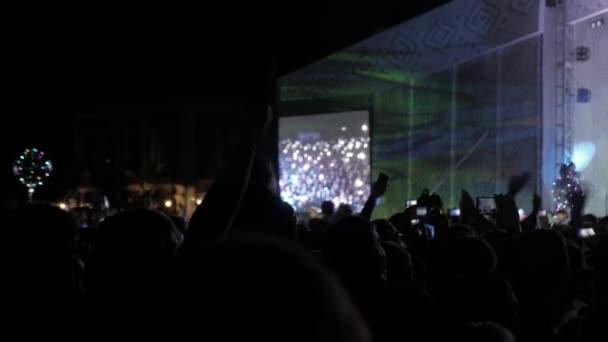 Menge Leute beim Musikkonzert. Jubelnde Menge nimmt Bilder auf einem Smartphone vor hellen Lebensstil bunte Bühnenbeleuchtung. Silhouetten von Konzert drängen sich vor hellen Bühnenbeleuchtung. Menge