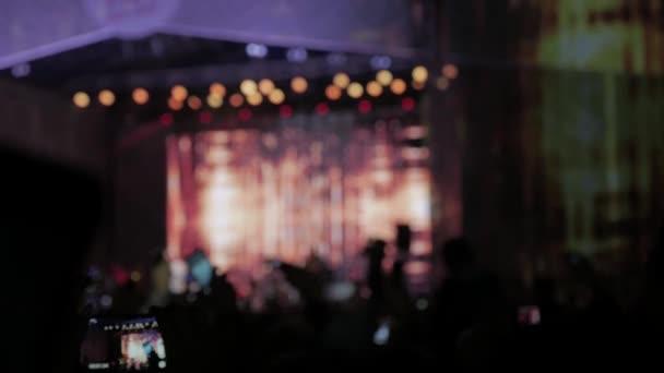 tömeg: koncert - nyári zenei fesztivál. Koncert tömeg, látogat egy megbeszél, emberek sziluettek látható, a hátország a színpad világítás. életmód a közönség nézi a koncert-színpad fogalma