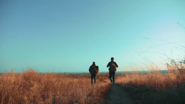 Two men traveler hiking with backpacks are walking lifestyle along the path climbing into the mountains. slow motion video. Tourist Hipster Hiker traveler on background view blue sky clouds go hiking