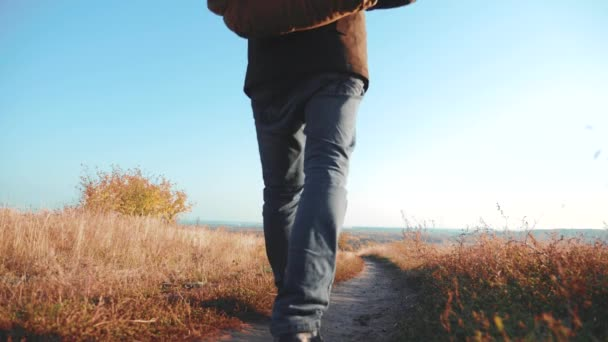 Two men traveler hiking with backpacks are walking along the path climbing into the mountains. slow motion video. Tourist Hipster Hiker traveler on background view blue sky clouds go hiking trip
