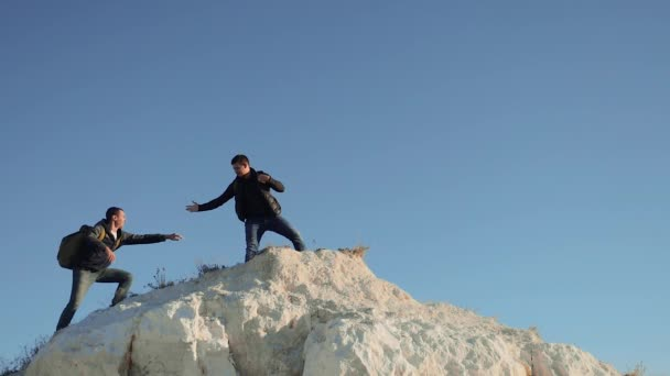 two men tourists hiking adventure lifestyle climbers climb the mountain . slow motion video. hiker walking goes on nature on the hill white rock. extreme outdoor activity sport concept tourist