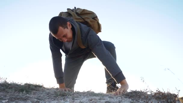 man rock climber struggles to the top of the mountain with difficulty striving for victory success goal. climber hiking adventure climbers climb the mountain . slow motion video. hiker walking on top