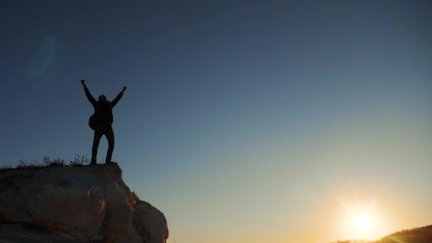 silueta tramp muž turisty ruce vzhůru horolezec leze Hora. pěší turistické dobrodružství horolezce slunce stoupání na horu. zpomalené video. Hiker sluneční světlo na vrcholu vítězství na kopci