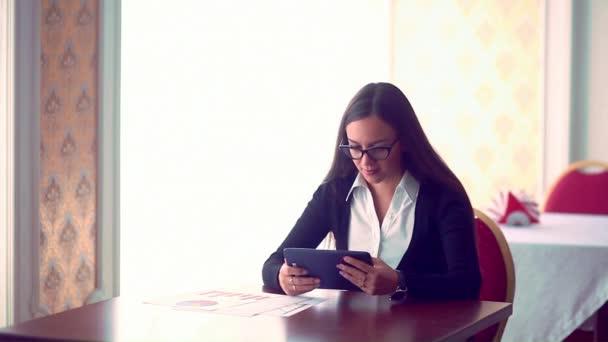 Üzletasszony dolgozó kávé a bolt dokumentumokkal. fiatal lány ült tabletta kávézóban. Súlyos fiatal nő, munkadokumentum Cafe életmód