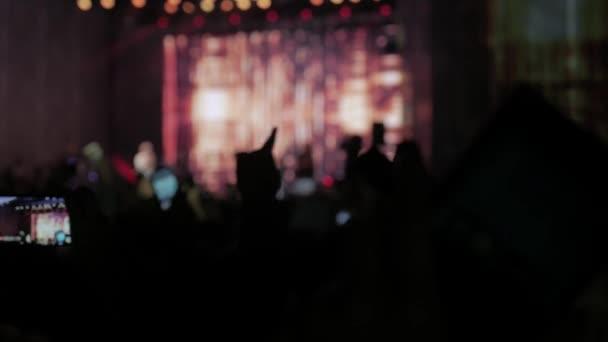 tömeg: koncert - nyári zenei fesztivál. Koncert tömeg, látogat egy megbeszél, emberek sziluettek látható, a hátország a színpad világítás. A közönség életmód figyeli a koncert-színpad fogalma