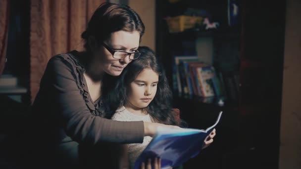 Holčička a dospělé ženy čtou knihu lekce se učí večer pohádku. matka a dcera číst knihu rodinné štěstí a jedno pojetí životního stylu