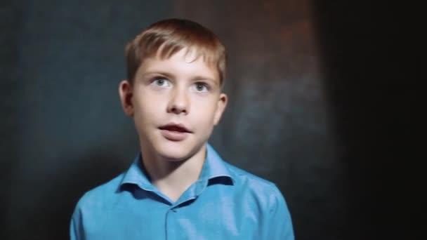 malý usměvavý chlapec mluví ve studiu na černém pozadí. Mladá blond Evropské neměcký podnikatel happy fun boy školák. koncepce pro podnikání boy teen životní styl