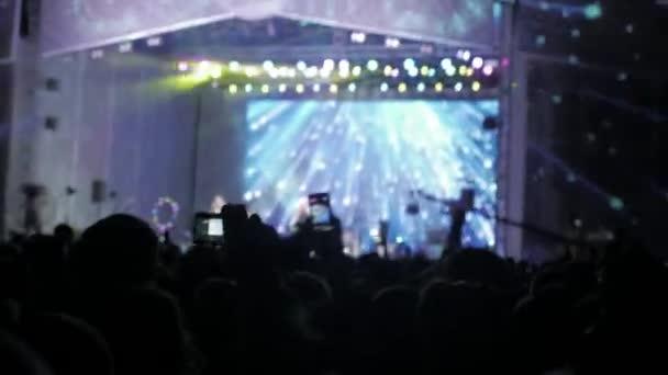 Tömeg emberek zene koncertet. Ujjongott életmód tömeg előtt fényes színes rivaldafény. sziluettek koncert tömeg előtt fényes színpadon lights. tömeg, az emberek egy koncert-koncepció