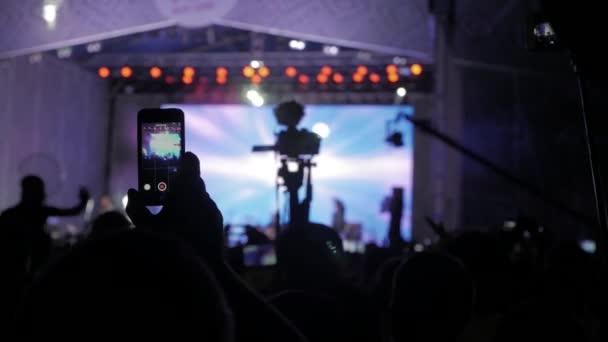 Tömeg emberek zene koncertet. Ujjongó tömeg előtt fényes színes színpad világítás egy okostelefon veszi a képek. sziluettek koncert tömeg előtt fényes színpadon lights. tömeg az emberek