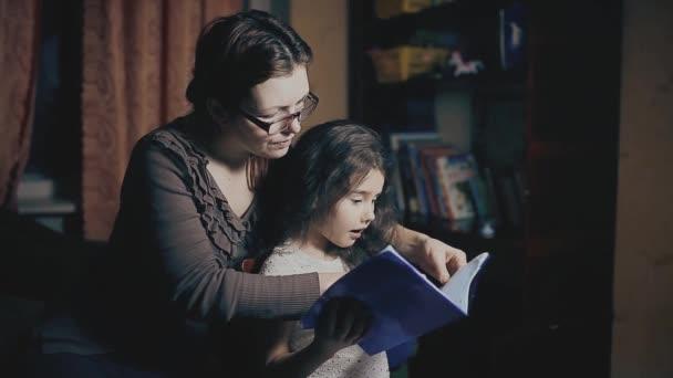 Holčička a dospělé ženy čtou knihu lekce se učí večer pohádku. matka a dcera číst knihu rodinné štěstí a koncepce péče o životní styl