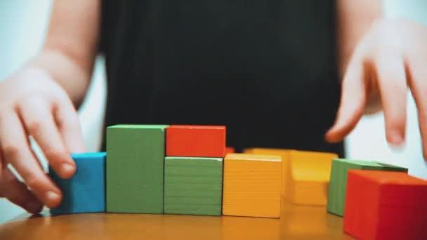malý chlapec sbírá kostky. malý chlapec hraje s hračky barevné kostky. dětství děti koncept životního stylu hry