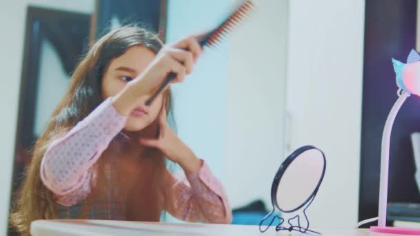 little brunette girl combing her hair looks in the mirror. Little Hispanic Girl Combing her Hair at home indoors. children childhood concept lifestyle