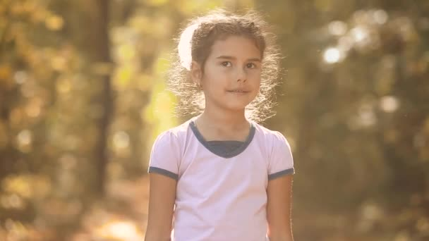 Little girl in the yellow autumn forest. Beautiful sunlight. little girl walks in autumn in the forest nature landscape lifestyle. children in nature concept