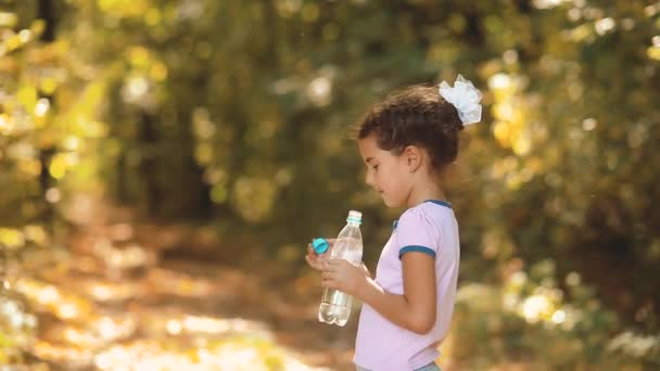 little girl drinks water from a plastic bottle in the autumn woods. little girl in the autumn beautiful forest is thirsty. little girl autumn concept lifestyle