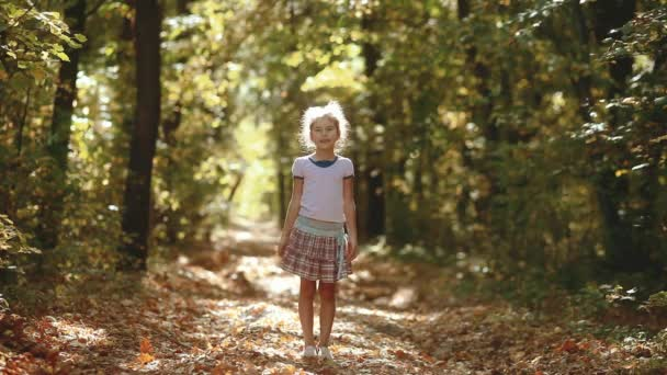 Little girl in the yellow autumn forest. Beautiful sunlight. little girl walks in autumn in the forest nature landscape. children in nature lifestyle concept