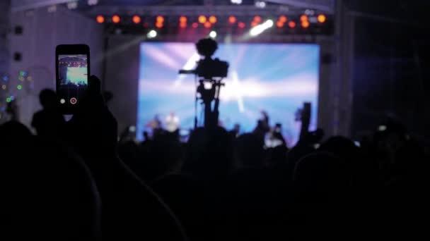 Menschenmenge bei Musikkonzert. Jubelnde Menge macht mit dem Smartphone Fotos vor bunten Bühnenlichtern. Silhouetten von Konzertbesuchern vor hellen Bühnenlichtern. Menschenmenge