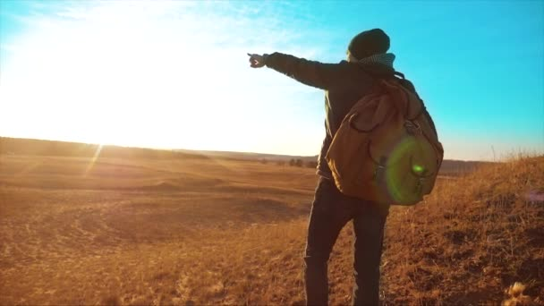 Silhouette hiker man of backpacker. steadicam motion video sunlight sunset person side view walking toward successful. lonely man with sunset background.Travel and lifestyle success concept the