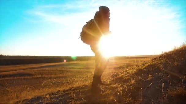životní styl silueta tramp muž s batohem. Steadicam motion video slunečního záření slunce osoba boční pohled k úspěšné. osamělý muž s slunce pozadím. Cestování a úspěch konceptu