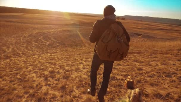 Silhouette hiker man of backpacker. steadicam motion video sunlight sunset person side view walking toward successful. lonely man with sunset background lifestyle. Travel and success concept the