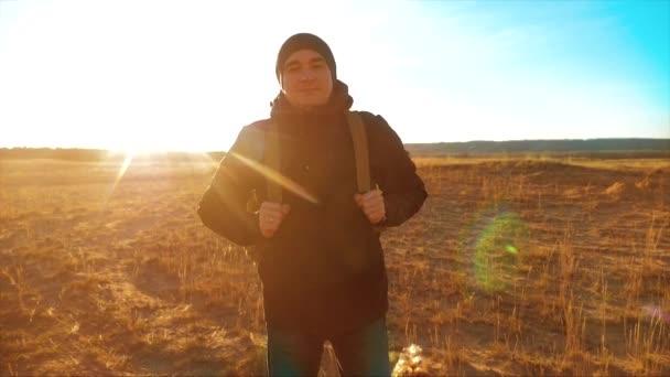 Silueta tramp muž s batohem. Steadicam motion video slunečního záření slunce osoba boční pohled chůzi směrem k úspěšné životní styl. osamělý muž s slunce pozadím. Cestování a úspěch konceptu