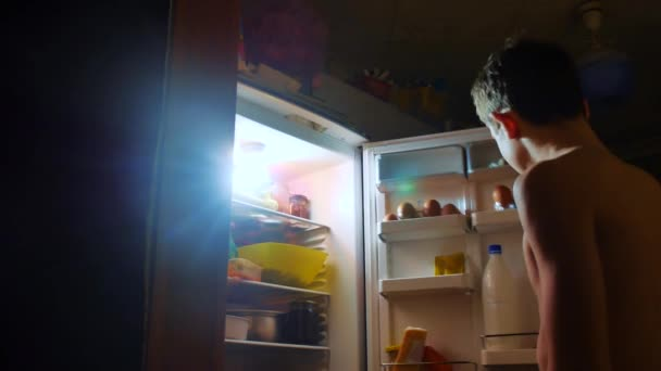 young boy eats hunger and gluttony from the refrigerator at night. teen boy looks into the fridge at night. lifestyle gluttony overweight overeating concept