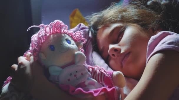 Rozkošná holčička spát v posteli, na pohovce a obejmout panence. malá brunetka spaní v noci v posteli miláčka životní styl. děti spát koncept
