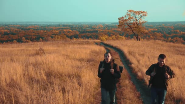 lidé turisté cestovat v přírodě životního stylu podzimní go silniční dobrodružství cesta. zpomalené video. dva tramp s venkovní batohy turistika. turistické koncepce cestovního ruchu muž