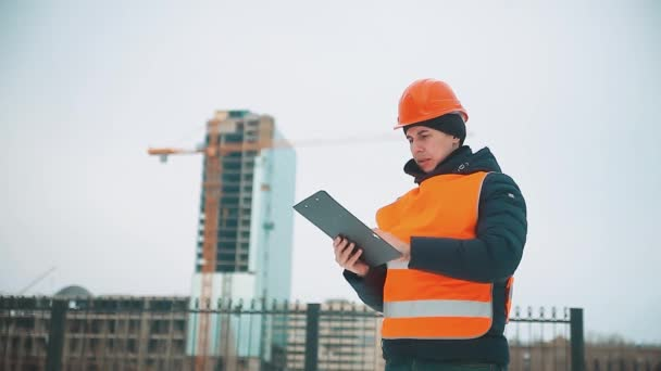 Engineering man Consulting People on construction site holding blueprint in his hand. Building inspector. Senior engineer Winter Jacket man in suit and helmet outdoor. construction concept winter man
