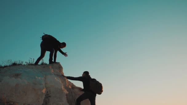 Týmová práce přátelství turistické pomoci každé jiné důvěry pomoci silueta v horách. Backpacker pomáhá svému příteli k lezení na skále. dva cestující pomoc natahovat ruku turistické pojetí životního stylu