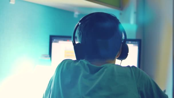 teen boy plays online game on computer via internet monitor in headphones. teenager man plays a video game at night. teen boy and computer lifestyle concept