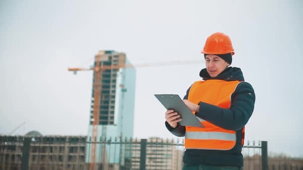 Engineering man Consulting People on construction site holding blueprint in his hand. Building inspector. Senior engineer Winter Jacket man in suit and helmet outdoor. construction concept winter