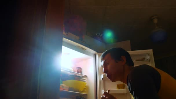man eats hunger and gluttony from the refrigerator at night. man looks into the fridge at night. gluttony lifestyle overweight overeating concept
