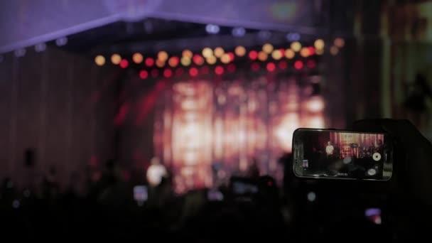 dav na koncertě - letní hudební festival. Koncert dav zúčastní koncertu, lidé siluety jsou viditelné, podsvícené Indikátory fáze. Diváci sledování životní koncert na jevišti konceptu