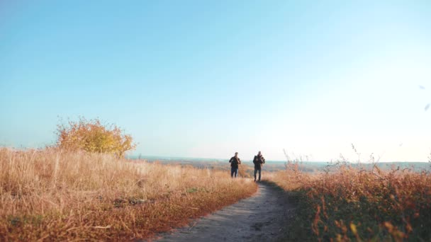 Two men lifestyle traveler hiking with backpacks are walking along the path climbing into the mountains. slow motion video. Tourist Hipster Hiker traveler on background view blue sky clouds go hiking