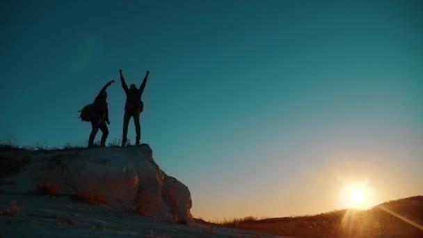 Týmová práce vítězství turistů. Dosahování cílů dva turisté na lyžích šťastný štěstí přírodní krajina. Týmová práce. Dva turisté turistům muži a pes s batohy procházky při západu slunce jít pěší výlet. pomalu